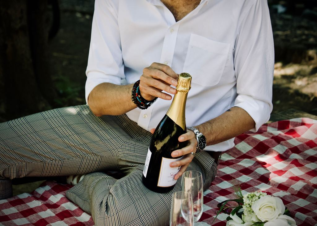 Mann macht ein Picknick mit Champagner
