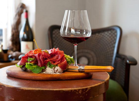 Ein Glas Rotwein und Schinkenbrot in der Weinbar Rheinton in Düsseldorf