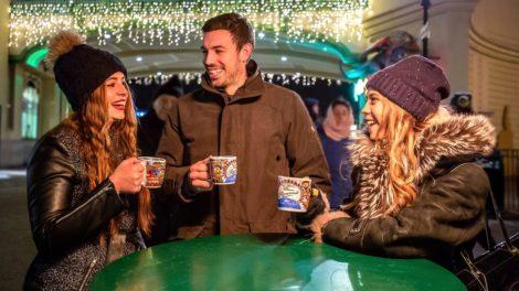 Besucher auf dem Weihnachtsmarkt trinken Glühwein