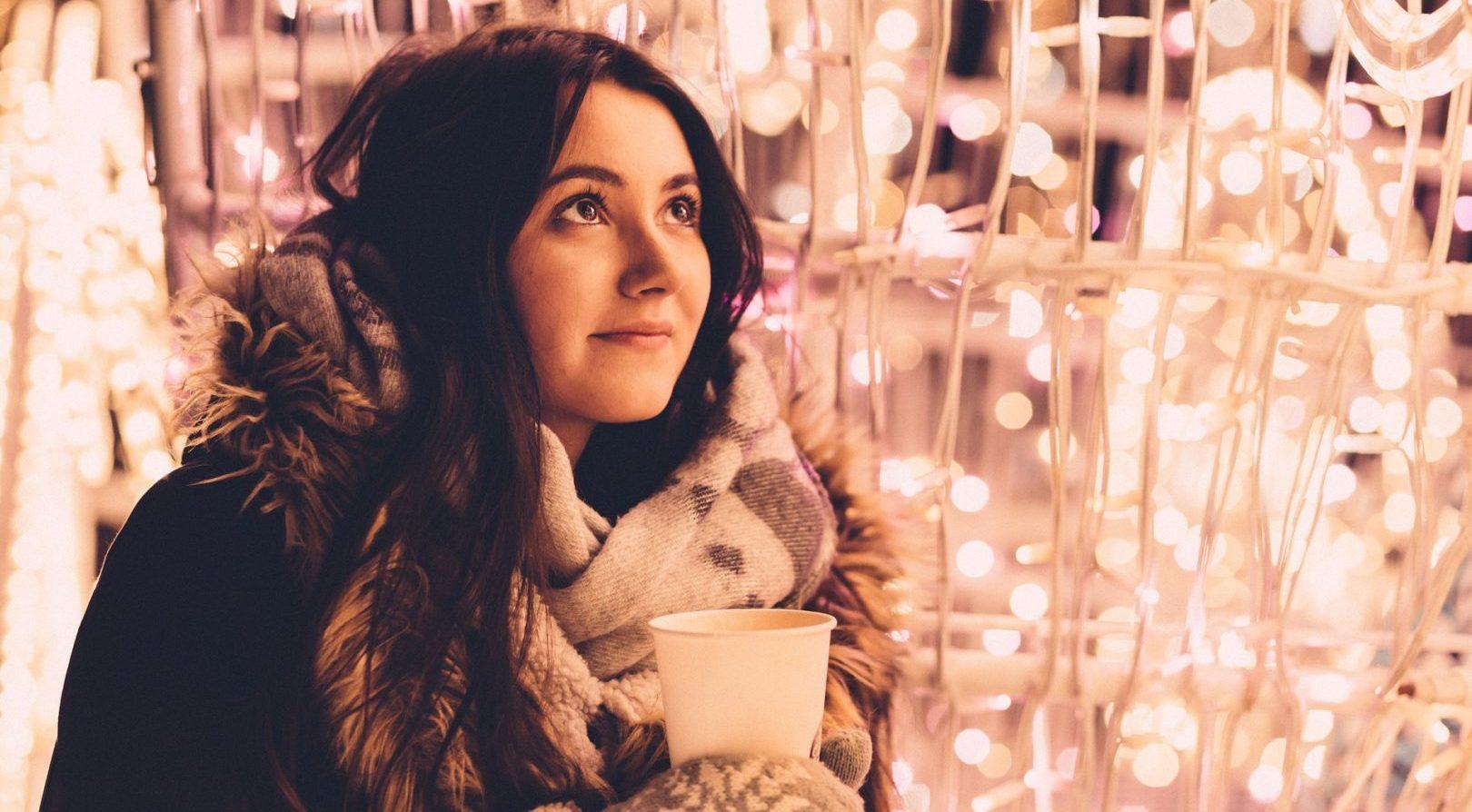 Frau trinkt weißen Glühwein auf dem Weihnachtsmarkt