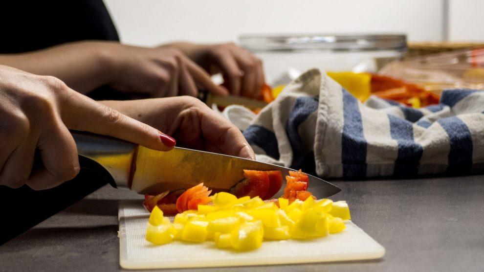 Frau schenidet Gemüse in der Küche