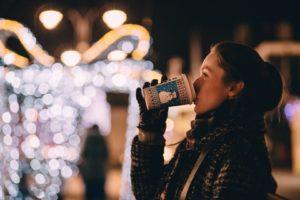 Frau trinkt auf dem Weihnachtsmarkt Glühwein
